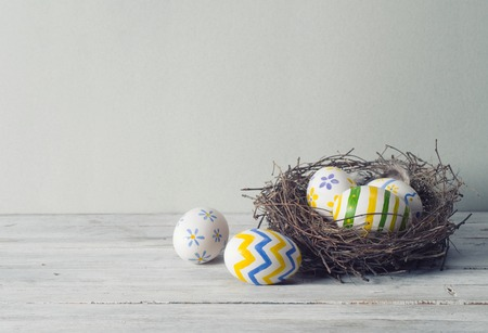 egg white: Easter eggs in the nest on rustic wooden background