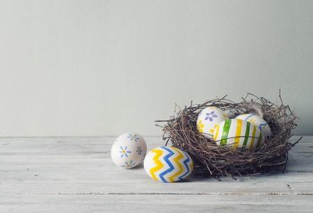 osterei: Ostereier im Nest auf rustikalem Holzuntergrund
