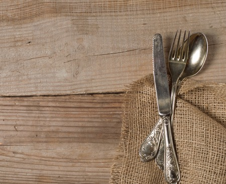 restaurant setting: old cutlery on wooden table