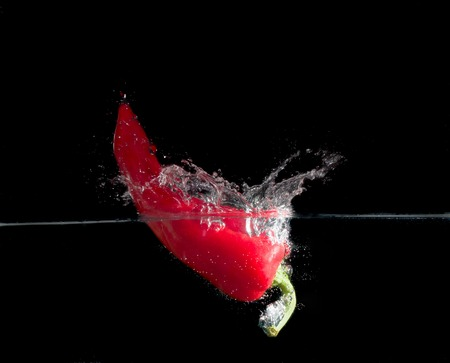 red paprika splash in water on black background. photo