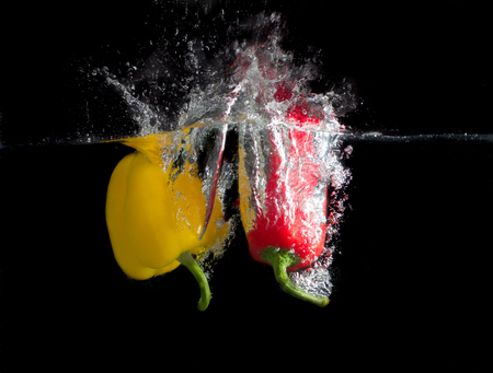 Yellow and red paprika splash in water on black background. photo