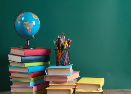 school desk: Books on the background of the school board