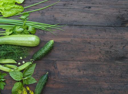 Groene groenten op houten achtergrond (erwten, peterselie, basilicum, komkommer, dille, ui, salade) Stockfoto