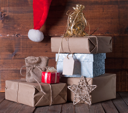 christmas presents: boxes with Christmas presents and santa hat on a wooden background Stock Photo