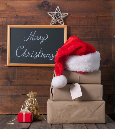 winter holiday: boxes with Christmas presents and santa hat on a wooden background Stock Photo