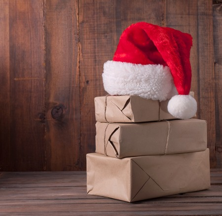 boxes with Christmas presents and santa hat on a wooden background Standard-Bild