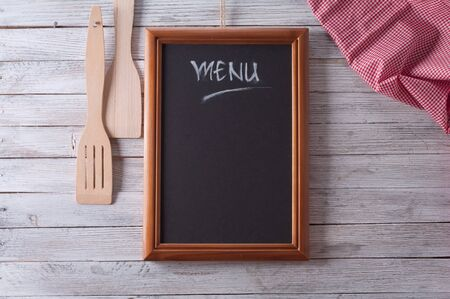 gastronomy: Blackboard on wooden surface and serving spoons