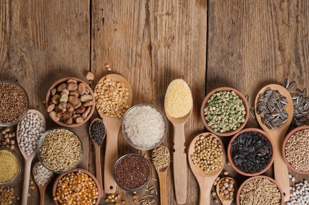 whole grains: Cereal grains , seeds, beans on wooden background.