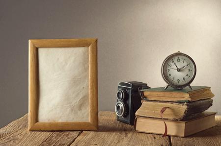 Natura morta con il nero orologio d'epoca e cornici per foto