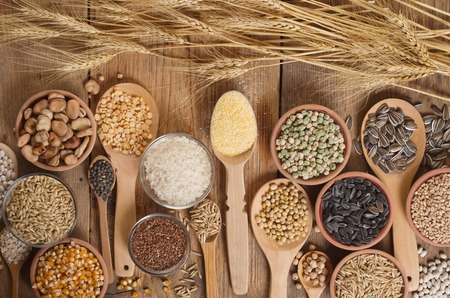 grain: Cereal grains , seeds, beans on wooden background.
