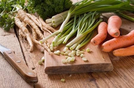 perejil: Las zanahorias, perejil y cebolla en la tabla de cortar