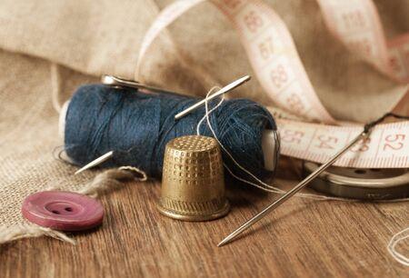 coser: dedal y agujas para coser en primer plano en un fondo de carretes de hilo. macro