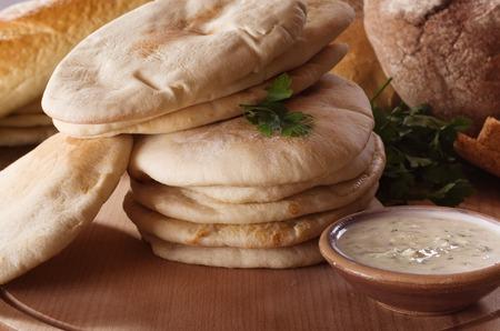 tzatziki: pita bread and tzatziki sauce on wooden table.
