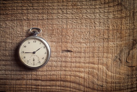 old hand: Old  pocket watch on wooden background. Stock Photo