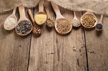 Les céréales, les graines, les haricots sur fond de bois.