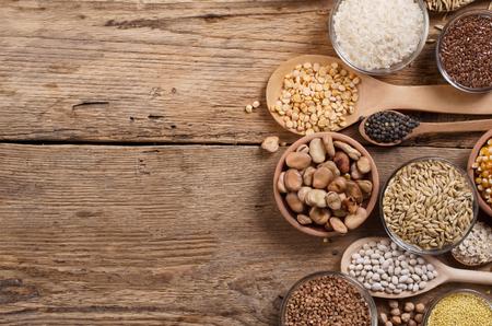 cereal: Los granos de cereales, semillas, frijoles sobre fondo de madera.