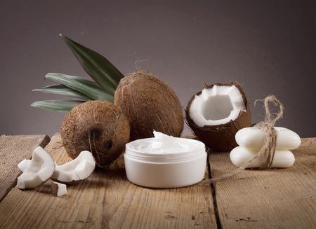 aceite de coco: aceite de coco y coco fresco en tabla de madera Foto de archivo