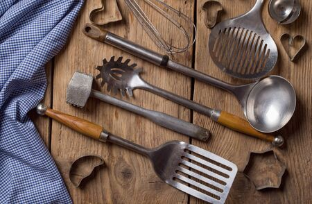 cooking utensil: Old kitchenware on wooden background.
