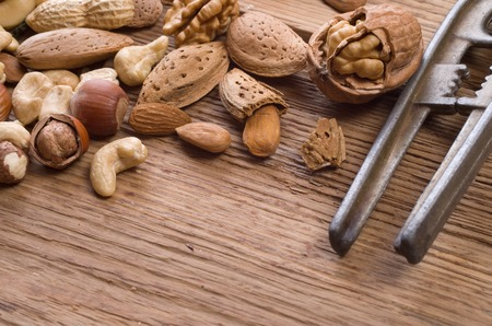 cashews: Nuts mix, with almond, cashews, pistachios, hazelnuts on wood background Stock Photo