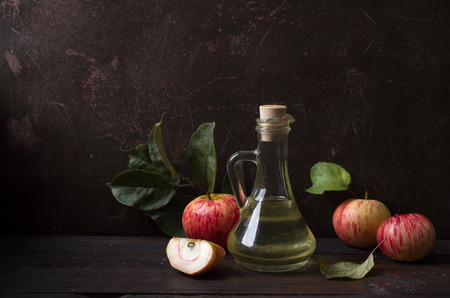 Glass of cider with apples and bottle on rustic wooden background Stok Fotoğraf