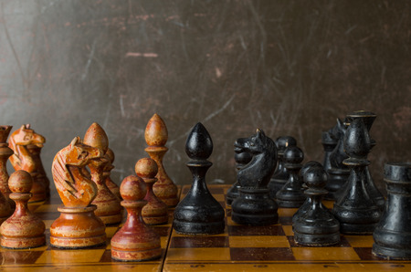 old and weathered chess board with chess pieces