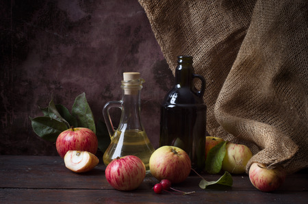 Glass of cider with apples and bottle on rustic wooden background Foto de archivo