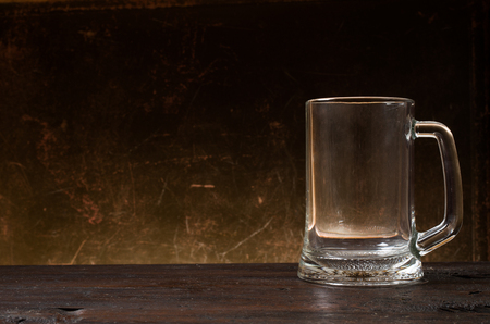 Empty beer glass on wooden table.
