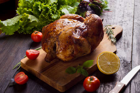 Whole roasted chicken with vegetables, on wooden table