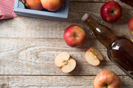 Cider with apples and bottle on rustic wooden background