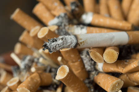Smoked cigarettes butts in a dirty ashtray Standard-Bild