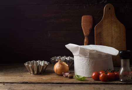 Chef's hat on an old wooden table. Conceptual background on the theme of food. Standard-Bild