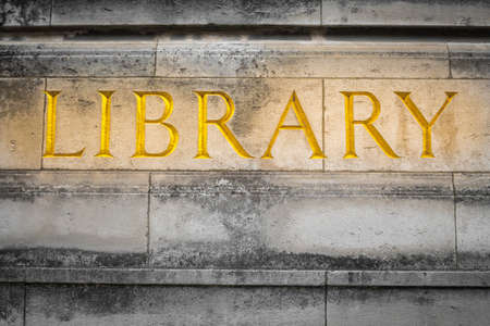 Public library exterior. Golden text engraved on a concrete wall background.