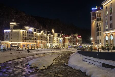 Russia, Sochi, Krasnaya Polyana. The resort of Rosa Khutor, hotels and shops at the Mzymta River at winter night. December 23, 2016. Editorial