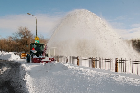 Snow removal from the side walk with a tractor with a snow blower machine in a winter sunny day Stock Photo
