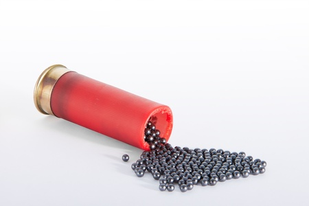 A shotgun red cartridge in horizontal position, open at the top  and the pellets drop out. Isolated in white. Stockfoto