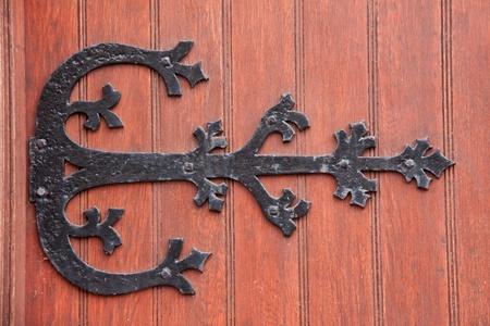 Wrought iron door decoration fixed on a massive wood door