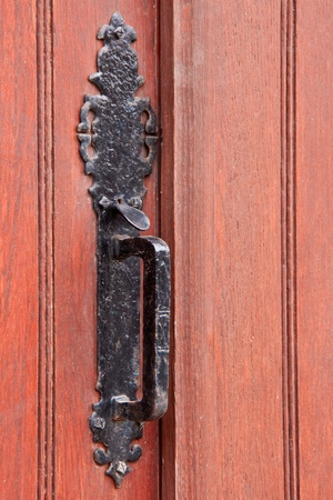 Wrought iron door handle fixed on a massive wood door