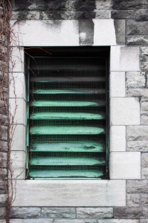 Window converted in a radiator grill, a beautiful element of architecture of an old building and a piece of air conditioner technology