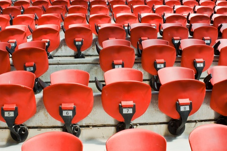 Red convertible chairs with numbers in an arena like a background... in the left side chair with number 6 from the second line is missing Stock Photo