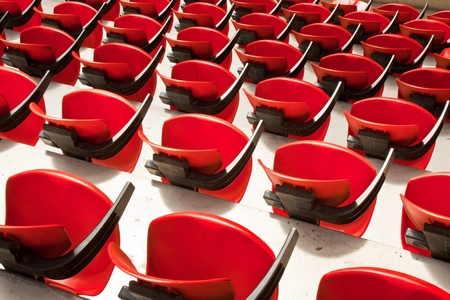 Red convertible chairs in an arena like a background