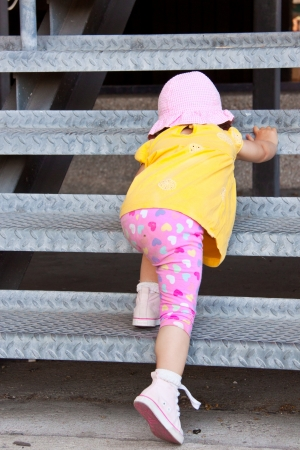 Little girl trying to escalate some metal stairs Stock Photo