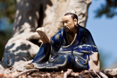 A little painted porcelain statue of a traditional Chinese man how read, standing down in harmony with the roots of o bonsai tree in the light of the sun Stock Photo