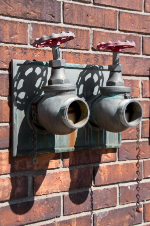 Old copper hydrant with two valve with rust and verdigris against a brick wall Stock Photo - 20437319