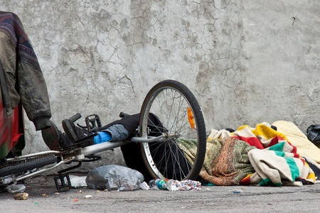Homeless sleeping on the sidewalk guarding his bicycle with foots in front of a cracked wall surrounded by a lot of mess, stumps and colored blankets