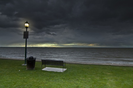 A public lighting lantern pole near a metal bench and a bin, on green grass, near the river side under a heavy stormy sky  At the skyline the shy is clear