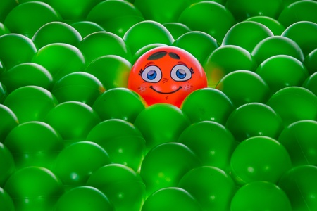 an orange happy ball with big blue eyes and two leafs in middle of green balls without personality