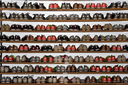 A rack full of different colors and size bowling shoes
