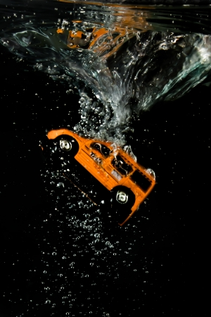The moment of immersion for an orange Taxi cab, bubbles, speed, reflections on the liquid surface and swirl in a black background Stock Photo