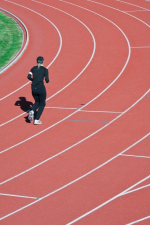 Beautiful young woman exercise jogging alone on athletic track on stadium