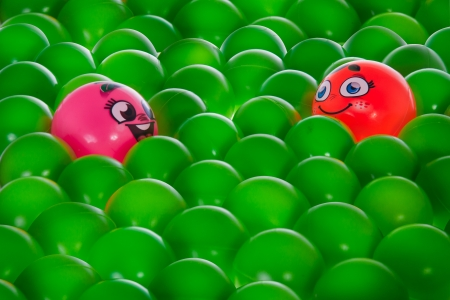 A pink happy ball with brown eyes communicate with An orange one in middle of green balls without personality  Stock Photo